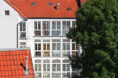 White house and hotel  with many windows, red roof tile and old big tree Stock Photos