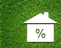 Interest Rate Symbol on Grass Background. White house and interest rate symbol on green grass background, business financial concept stock image