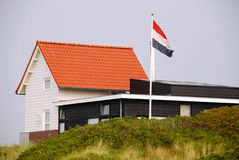 White house on the Island of Vlieland. A white house and the Dutch flag on the Frisian Island of Vlieland. The Frisian Islands, also known as the Wadden Islands Royalty Free Stock Image
