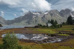 White house and mirror lake with view to snow mountains and sea in the Norway at summer royalty free stock photos