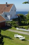 White house near the sea. White, wooden house in a garden near the sea in Loshavn near Farsund in Vest-Agder, Norway Stock Photos