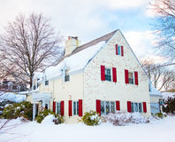 White House with Red Shutters. A pretty painted brick home with red shutters covered in snow stock images