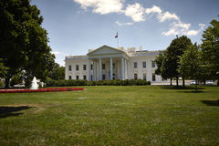 White house sunny day. A landscape of the white house on a sunny summer afternoon. Grasses and garden can be seen in forground. Trees frame the image Royalty Free Stock Photo