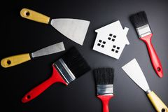 White house toy and paint brush, painters equipment on black bac. Kground with copy space.Real estate concept, New house concept, Finance loan business concept Royalty Free Stock Photography