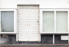 White house wall with closed door and windows Stock Photo