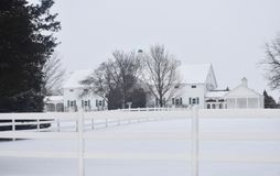 White house and picket fence in winter. White house with white picket fence in snow Royalty Free Stock Photo
