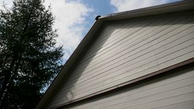 White house wooden roof with black roof with blue sky. And wood stock video footage