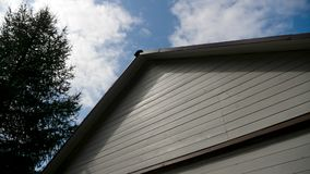 White house wooden roof with black roof with blue sky. And wood stock video
