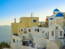 White houses, churches and blue domes in Oia village Royalty Free Stock Images