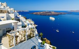 White houses of Fira, Santorini with Santorini`s famous volcano and ships in background Royalty Free Stock Photo