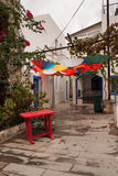 White houses in Greek style. The narrow streets of Bodrum. Homes residents. Colorful umbrellas hanging upside down. Small red wood. White houses in Greek style stock image