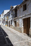 White houses in Ronda, Andalusia Spain. View a narrow street with white houses in Ronda, Andalusia Spain on a hot summer afternoon Royalty Free Stock Images
