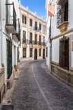 White houses in Ronda, Andalusia Spain. View a narrow street with white houses in Ronda, Andalusia Spain on a hot summer afternoon Royalty Free Stock Photography