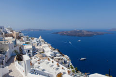 White houses of Santorini with Santorini`s famous volcano in the background Royalty Free Stock Photo