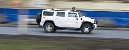 White huge hummer suv car driving fast, rushing forward Royalty Free Stock Images