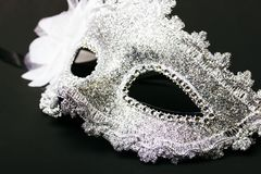 White human carnival mask isolated on dark background. Close-up Royalty Free Stock Image