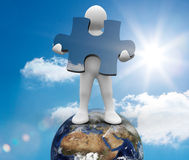 White human representation standing on earth. And holding a jigsaw piece Royalty Free Stock Image