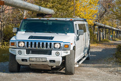 White Hummer H2 limousine at the rural street Stock Photos