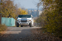 White Hummer H2 limousine at the rural street Royalty Free Stock Images