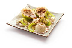 White ice-cream balls with kiwi, pear, chocolate. White ice-cream balls with kiwi, pear and chocolate in squared plate over white background Stock Images