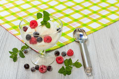 White ice cream in a glass with raspberry and currant berries an. D mint leaves on checkered napkin and wooden desk Royalty Free Stock Images