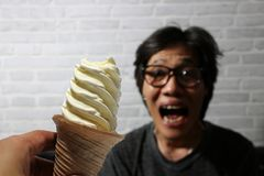 White ice cream spiral shape on the scoop in hand and out focus the man excited, want to eat. royalty free stock images