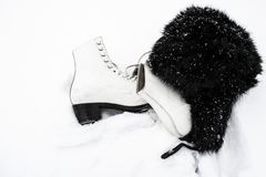 White ice skates and a black fur cap in the snow. royalty free stock images