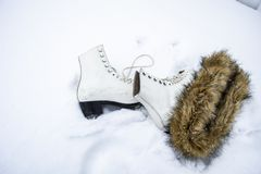 White ice skates and a brown fur scarf in the snow. stock images