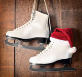 White ice skates for figure skating, hanging on wooden background Royalty Free Stock Photo