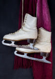 White ice skates hanging with red and pink wool scarf Stock Image
