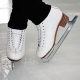 White Ice Skates on Ice Rink. Woman's Legs in White Ice Skates on Ice Rink Royalty Free Stock Image