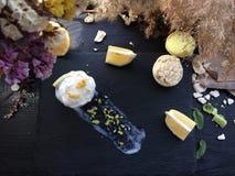 White icecream with lemon on a black tray Stock Photos