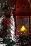White icicle hanging on a branch of a Christmas tree against a red lantern with a candle. Christmas and New Year Stock Images