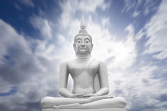White image of Buddha with blue sky and cloud in background, light effect added ,filtered image,radial blurred sky,moving cloud. White image of Buddha with blue royalty free stock image