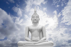 White image of Buddha with blue sky and cloud in background, light effect added , prachuapkhirikhan,thailand,filtered image.  royalty free stock photography