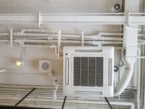 White Industrial air conditioner cooling pipe with plumbing at ceiling. Ventilation system ceiling air duct.  royalty free stock photography