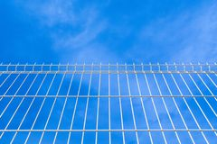 White industrial fence to the sky stock image