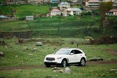 White Infiniti FX30d turbo diesel SUV Car On Off Road In Spring Stock Image
