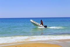 A white inflatable motor boat with a man on board moves along the shore.  Royalty Free Stock Image