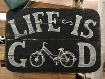 White inscription Life is good on an old wooden black board with a bicycle stock photo