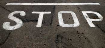 The white inscription of STOP on road Royalty Free Stock Image