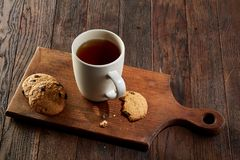 Cup of tea with cookies, workbook and a pencil on a wooden background, top view. A white inside and brown outside porcelain cup of tea with tasty chocolate chips Royalty Free Stock Photo