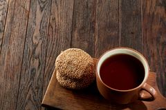 Cup of tea with cookies, workbook and a pencil on a wooden background, top view. A white inside and brown outside porcelain cup of tea with tasty chocolate chips Royalty Free Stock Image