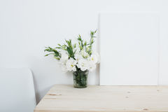 White interior decor, fresh natural flowers in vase and canvas stock photo