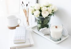 White interior decor with new hand-made candle and bouquet of fr. Esh roses, luxury home decorations in daylight closeup Royalty Free Stock Images