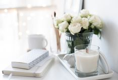 White interior decor with new hand-made candle and bouquet of fr. Esh roses, luxury home decorations in daylight closeup Stock Images