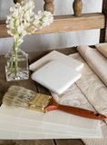 White interior decoration plan. White color cards, fabric swatches and tiles on an old, rustic, unpainted chair with a paintbrush and white flowers Stock Photos