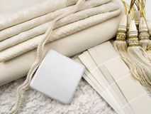 White interior design plan. White paint color swatches, upholstery material samples, a ceramic tile and tassels on white rough marble Royalty Free Stock Images