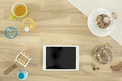 White Ipad on Brown Surface Near Clear Cookie Jar Stock Photo