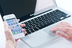 White iphone 4 4s. In women's hands next to macbook pro Royalty Free Stock Image